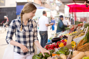 woman looking at vegetables at a farmers market stall